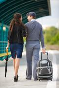 Stock Photo of rear view of amorous couple walking down station and chatting outdoors
