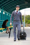 Stock Photo of handsome man walking down railway station with umbrella and baggage with sad gir