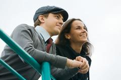 below view of caucasian couple looking forward with smiles outdoors - stock photo