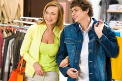 happy man and his girlfriend with paperbags looking at something in the shopping - stock photo