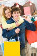 Stock Photo of attractive woman embracing her boyfriend while both looking at camera with smile