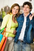 portrait of loving couple chosing something in trade center and smiling - stock photo