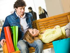 Image of tired girl lying on bench in market with her boyfriend sitting near by Stock Photos