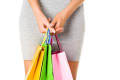 Image of shopaholic hands with three bags of green, yellow and pink color Stock Photos