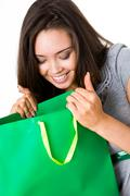 Photo of surprised female opening paperbag with gift and looking into it Stock Photos