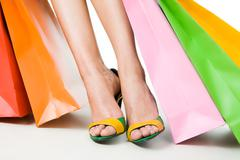 Stock Photo of close-up of feminine legs in shoes with paperbags near by over white background