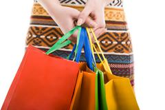 close-up of female hands with colorful shopping bags - stock photo