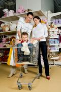 portrait of husband and wife looking at their joyful son in toy department - stock photo