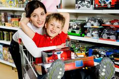 Portrait of pretty woman embracing her son and both looking at camera with smile Stock Photos