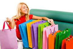 portrait of smiling blonde sitting on sofa with several colorful shoppingbags - stock photo