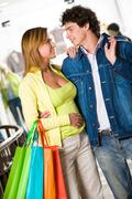 portrait of amorous couple looking at each other with smiles during shopping - stock photo