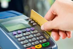Close-up of payment machine while human hand keeping plastic card in it Stock Photos