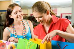 Photo of two friends looking through their shoppings with smiles in the mall Stock Photos
