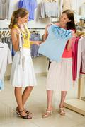 portrait of glamorous girls holding tanktops in hands while choosing new clothes - stock photo