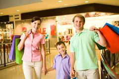 portrait of husband and wife with their son after shopping - stock photo