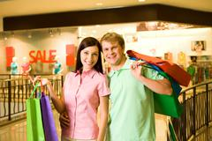 portrait of shopaholics holding paperbags and smiling at camera - stock photo