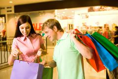 Portrait of pretty female showing bags to happy man after shopping Stock Photos