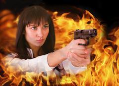 Aggressive girl shoots from flame.  - stock photo