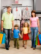 Portrait of family walking down shopping mall after good shopping Stock Photos