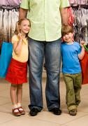 portrait of happy girl and boy embracing their father in the mall - stock photo