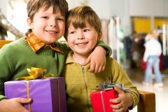 Portrait of cute boy with giftbox embracing his brother in supermarket Stock Photos