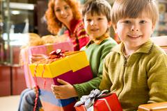 happy boy with gift in hands sitting in supermarket on background of his brother - stock photo