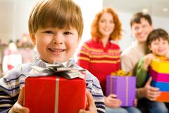 portrait of glad boy with present looking at camera on background of family memb - stock photo