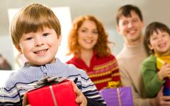 portrait of glad boy with present looking at camera on background of his parents - stock photo