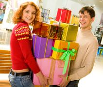 portrait of shopaholics holding heap of presents and smiling at camera - stock photo