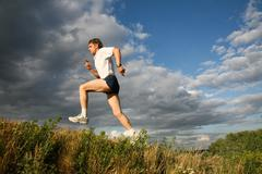view of athlete jumping on the background of sky - stock photo