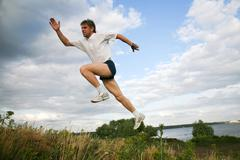 Stock Photo of horizontal image of active man jumping near lake
