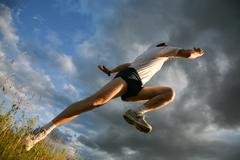 View from below: athlete raising leg and hand Stock Photos
