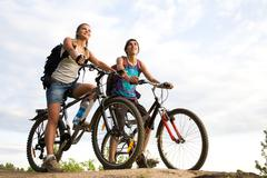 Image of sporty couple on bicycles outdoors against cloudy sky Stock Photos