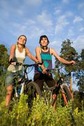 Couple of cyclers on their bikes in the countryside on hot summer day Stock Photos