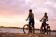 figures of happy couple standing on seashore with their bicycles and enjoying su - stock photo