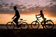 Silhouettes of couple riding their bicycles on seashore at sunset Stock Photos