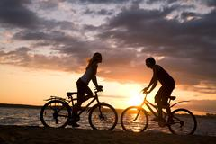silhouettes of couple opposite each other on their bicycles by the sea at sunset - stock photo