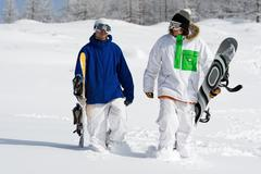 portrait of two sportsmen with snowboards walking down snowdrift - stock photo