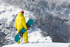 Stock Photo of rear view of snowboarder standing in snowdrift in winter