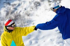 Portrait of two guys with snowboards climbing down snow-covered mountain Stock Photos