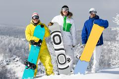 portrait of three happy young men with snowboards looking at camera - stock photo