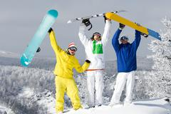 portrait of three happy young snowboarders raising their arms - stock photo