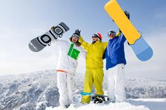Portrait of three successful snowboarders raising their arms on mountain top Stock Photos
