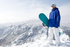 portrait of happy sportsman with snowboard standing on top of mount - stock photo