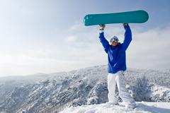 portrait of joyful sportsman with snowboard standing on top of mount - stock photo