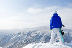 rear view of sportsman with snowboard standing on top of mount - stock photo