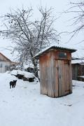 rural toilet and dog in winter - stock photo