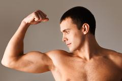 image of powerful man looking at his muscles during exercise - stock photo
