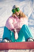 photo of laughing female wearing snowboarding clothes sitting on ground - stock photo