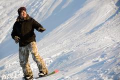 Photo of cheerful man standing on snowboard at winter resort Stock Photos